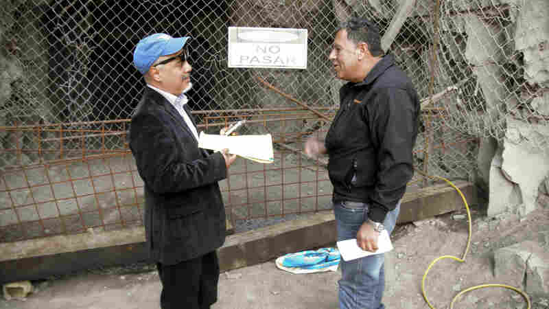 Hector Tobar (left) stands in front of a mine entrance with Luis Urzúa, the head of the shift of trapped miners, in 2011 at the San Jose Mine.