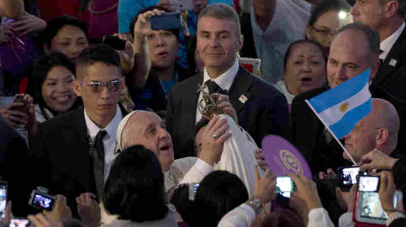 Pope Francis holds a Virgin Mary statue as he arrives at the Mall of Asia arena in Manila, Philippines, on Friday. The pontiff has issued a strong statement supporting the church's teachings on artificial contraception.