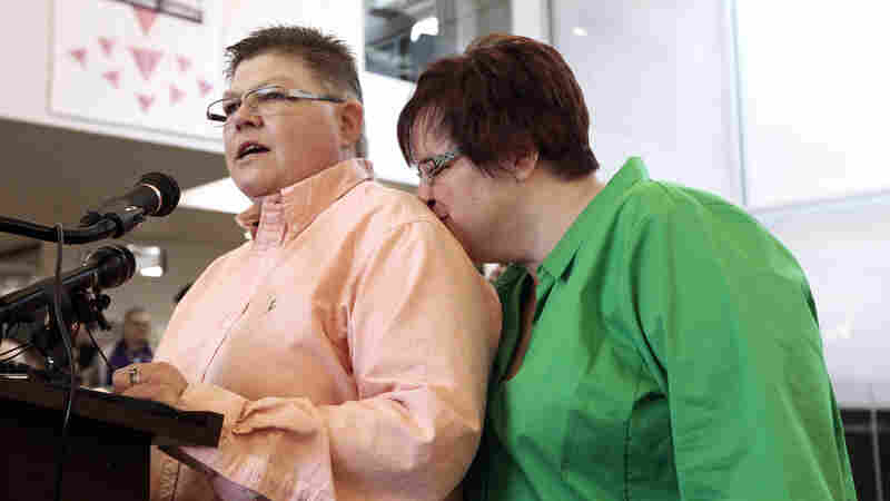 Jayne Rowse (left) speaks as April DeBoer kisses her during a news conference in Ferndale, Mich., on March 21, 2014. An appellate court upheld Michigan's — and three other states' — bans on gay marriage. The Supreme Court said Friday it will review the appellate court's decision. DeBoer and Rowse are the Michigan couple in the case.
