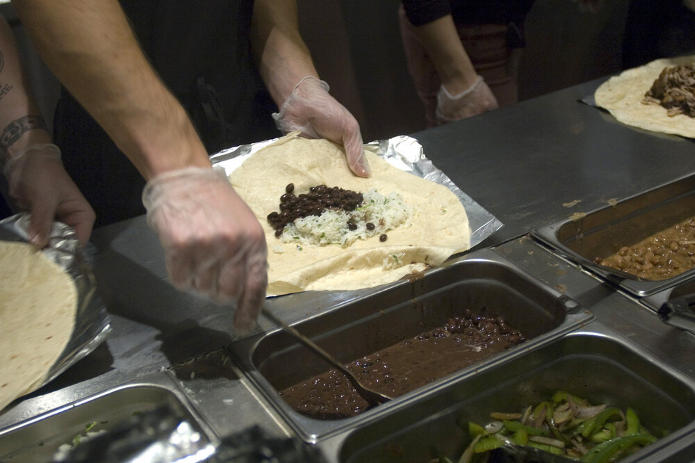 Workers prepare burritos at a Chipotle Mexican Grill in New York. The restaurant chain has stopped serving pork in about one-third of its U.S. locations.