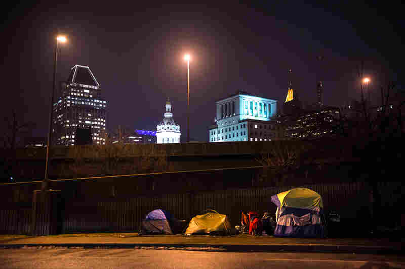 "Tents set up by the side of a freeway in Baltimore, as seen during Simmons' ""justice walk"" with a group of Johns Hopkins students."