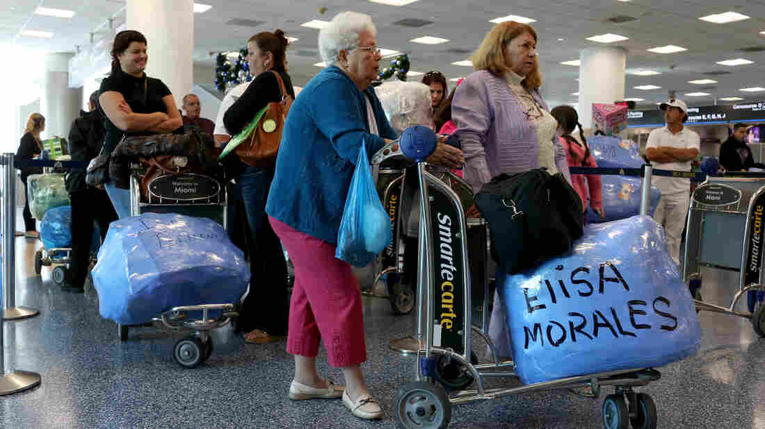 Travelers wait to check in for charter flights from Miami to Havana at Miami International Airport.
