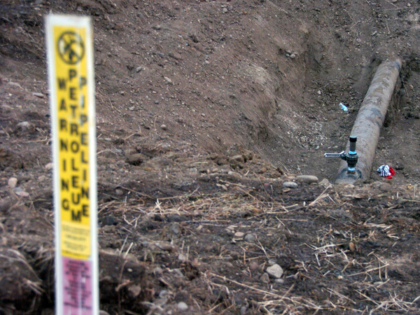 A warning sign shows the location of a 12-inch oil pipeline owned by Bridger Pipeline Co. that spilled up to 50,000 gallons of crude along the Yellowstone River near Glendive, Mont.