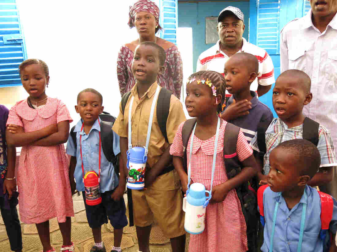 Children and teachers sing the national anthem on Monday morning, their first day in school since July.