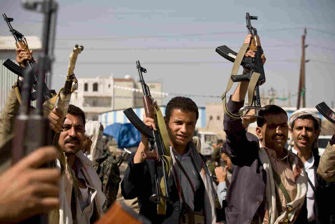 Houthi rebels in Yemen hold up their weapons during clashes near the presidential palace in the capital, Sanaa, on Monday. The rebels reportedly seized the presidential palace on Tuesday, and the fate of President Abed Rabbo Mansour Hadi was not clear.