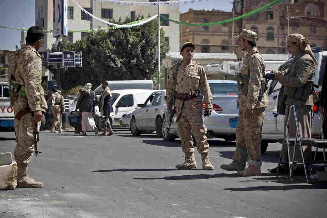Shiite Houthis wearing Yemeni army uniforms stand guard on a street leading to the presidential palace in Sanaa, Yemen, on Wednesday.