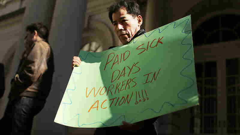 One demonstrator advocates for paid sick leave at a 2013 rally outside New York's city hall. The city is now one of several in the U.S. to have passed a measure mandating paid sick days.