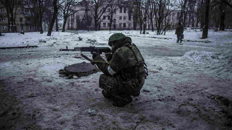 A Russian-backed separatist rebel aims his machine gun while protecting a supply position in the Kievsky district, about a mile from the Airport, in Donetsk, Ukraine, on Thursday.