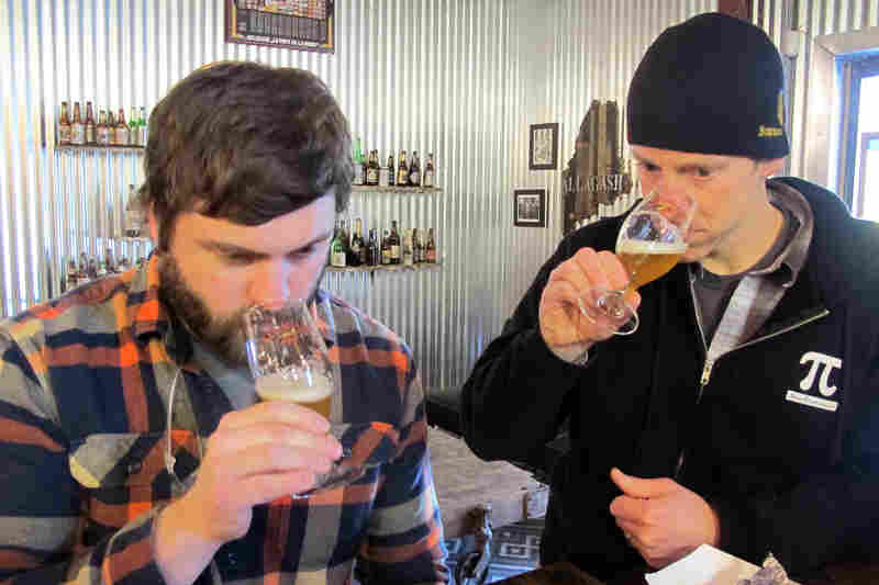 Allagash microbiologist Zach Bodah (left) and Jason Perkins, head brewer (right), assess the aroma of a beer made with the local Brettanomyces strain.