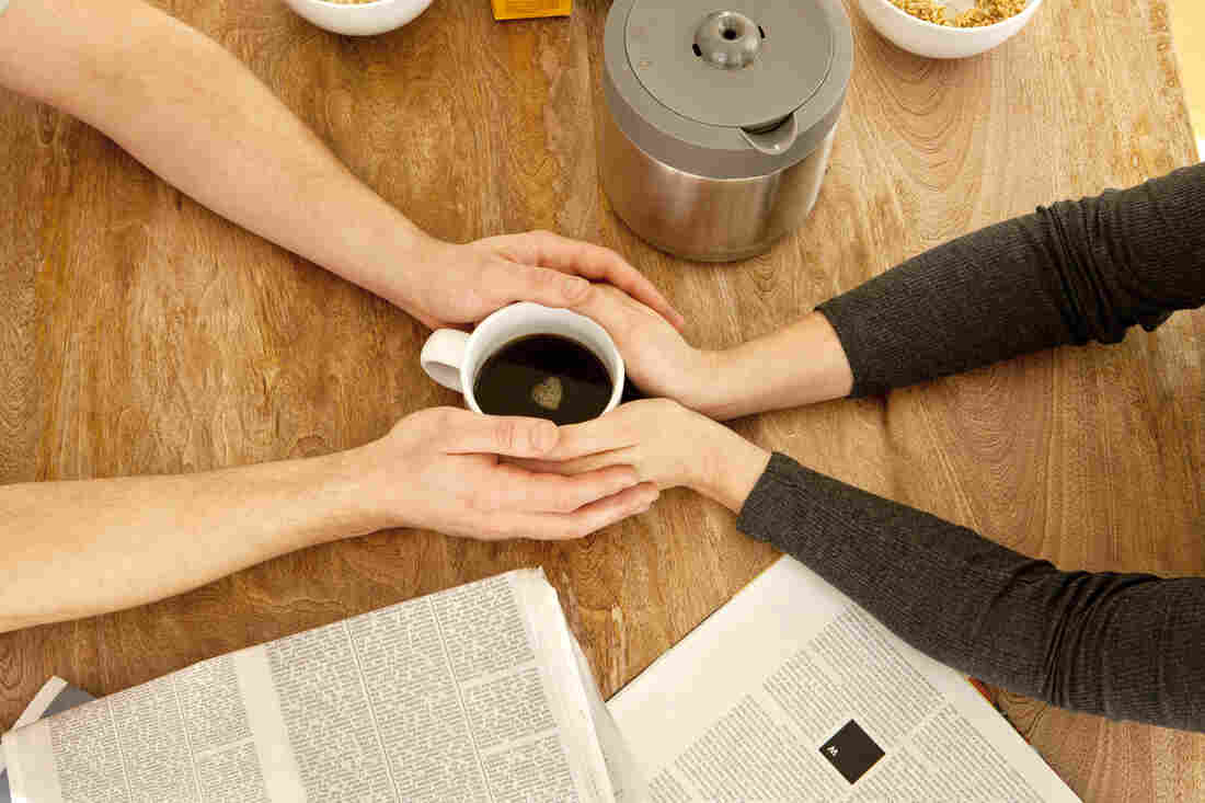 Couple's hands wrapped around one cup of coffee.