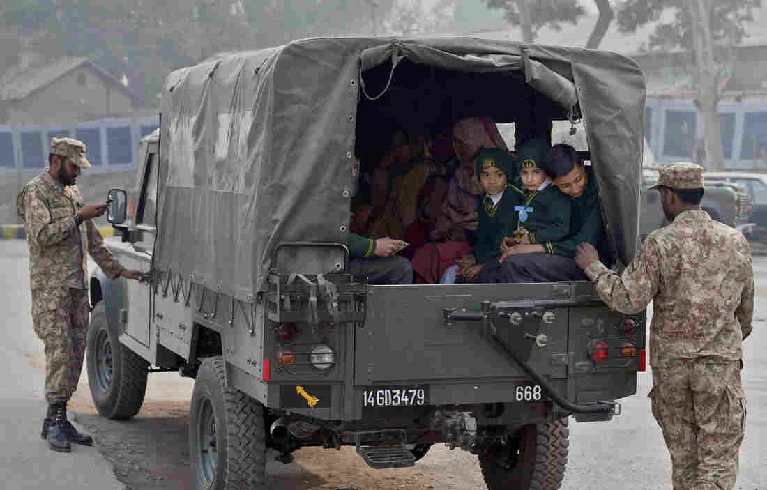 Pakistani soldiers escort students as they leave the Army Public School in Peshawar on Jan. 12. The school has reopened after last month's attack by the Pakistani Taliban that killed more than 130, most of them teenage students.