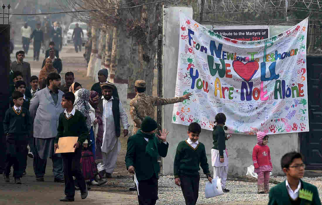 Pakistani parents leave the Army Public School with their children after it was reopened on Jan. 12. Most of the surviving students and teachers returned to the school.