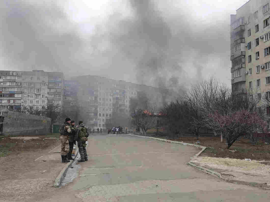 Ukrainian servicemen stand guard on a street near a burning building after a shelling by pro-Russian rebels of a residential sector in Mariupol, eastern Ukraine, on Saturday.