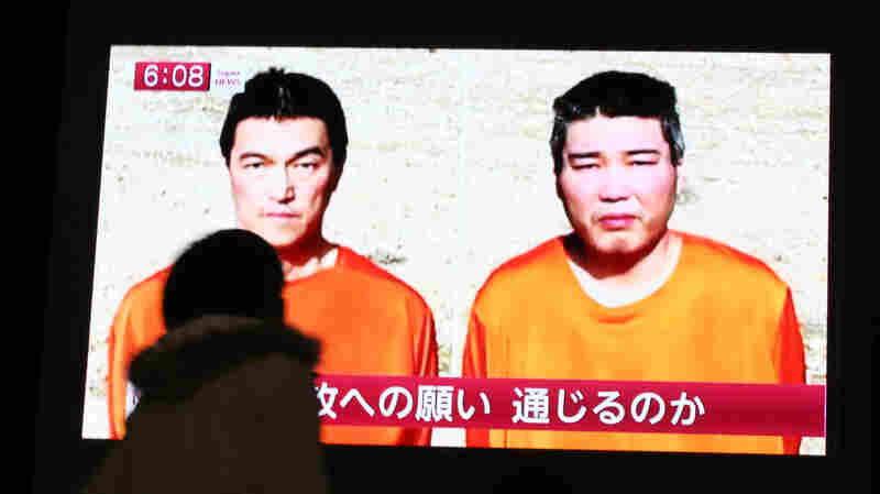 A passerby watches a TV news program reporting two Japanese hostages, Kenji Goto, left, and Haruna Yukawa, held by the Islamic State group, in Tokyo, on Friday.