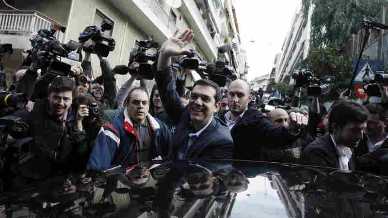 Alexis Tsipras, center, leader of Greece's Syriza left-wing main opposition waves to his supporters after voting at a polling station in Athens, on  Sunday.