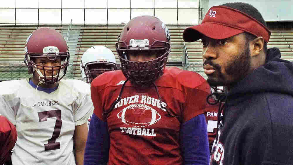 Coach Corey Parker talks with his players during football practice at River Rouge High.
