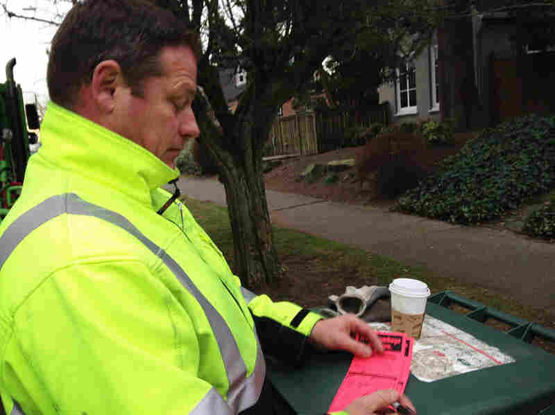 Recology CleanScapes driver Rodney Watkins issues a red tag — the scarlet letter of food waste in Seattle.