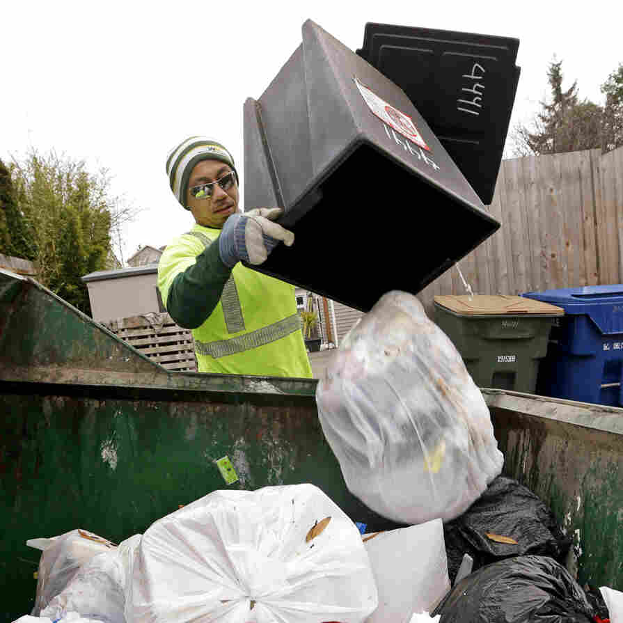 Seattle garbage collector Anousone Sadettanh empties a small residential garbage bin into his truck in 2014. It is now illegal to toss out food with the trash in the city. Residents will get warning tags for now; the city will start imposing fines in July.