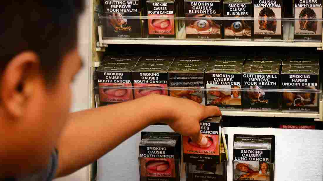 An employee in a Sydney bookshop in 2012 adjusts packaged cigarettes, which have to be sold in identical olive-brown packets bearing the same typeface and largely covered with graphic health warnings.