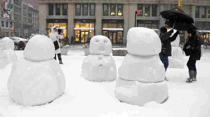 """People walk past and take pictures of Swiss artist Peter Regli's """"Snow Monsters 2015"""" during a storm in New York City Monday. Areas of New York and neighboring states are expected to get up to 2 feet of snow in a large and dangerous storm."""