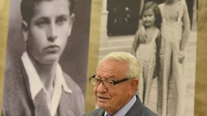 Jack Mandelbaum, a Holocaust survivor from the Polish city of Gdynia, poses in front of a photograph showing him as a youth.
