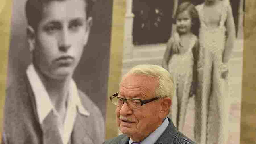 Jack Mandelbaum, a Holocaust survivor from the Polish city of Gydnia, annexed by Nazi Germany during World War II, poses in front of a photograph showing him as a youth.