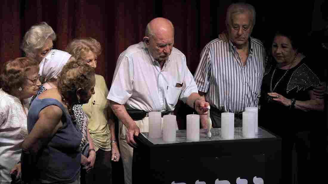 Holocaust survivors light candles during a ceremony at the Asociacion Mutual Israelita Argentina (AMIA) building for Holocaust Victims Memory Day in Buenos Aires, the site of a deadly bombing two decades ago.