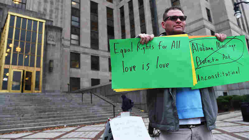 Robert Bate of Birmingham holds signs endorsing same-sex marriage outside the Jefferson County Courthouse in Birmingham, Ala., Monday. On Tuesday, the chief justice of the state's Supreme Court said federal courts are overstepping their jurisdiction in deciding cases about the issue.