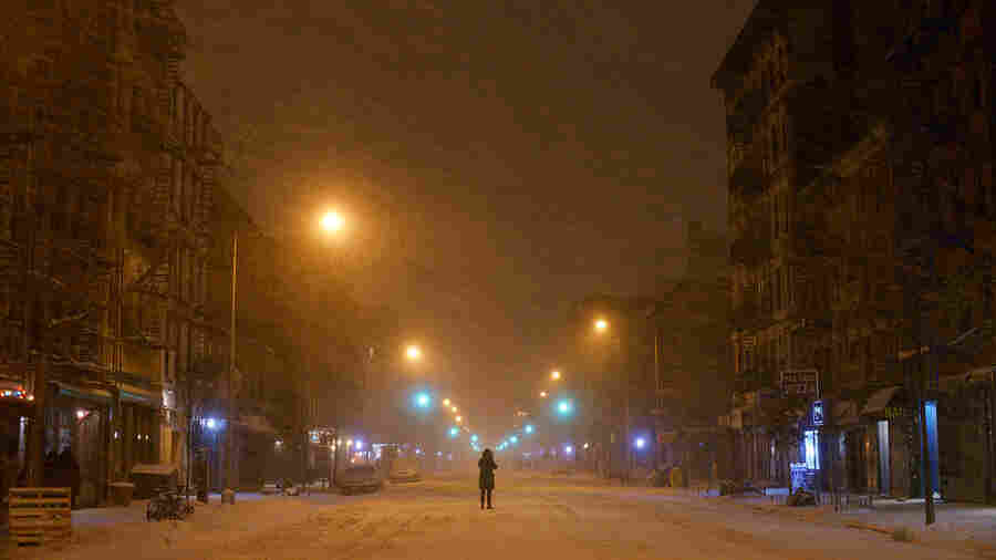 A person stands in the middle of snow-covered Avenue A in the East Village neighborhood of New York, early Tuesday morning.