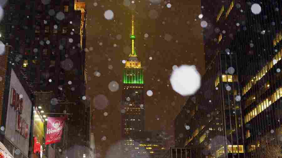 Snow falls around the Empire State Building in midtown Manhattan. Tens of millions of people along the Philadelphia-to-Boston corridor are settled in as a fearsome storm swirls in with the potential for hurricane-force winds and 1 to 3 feet of snow that could paralyze the Northeast for days.