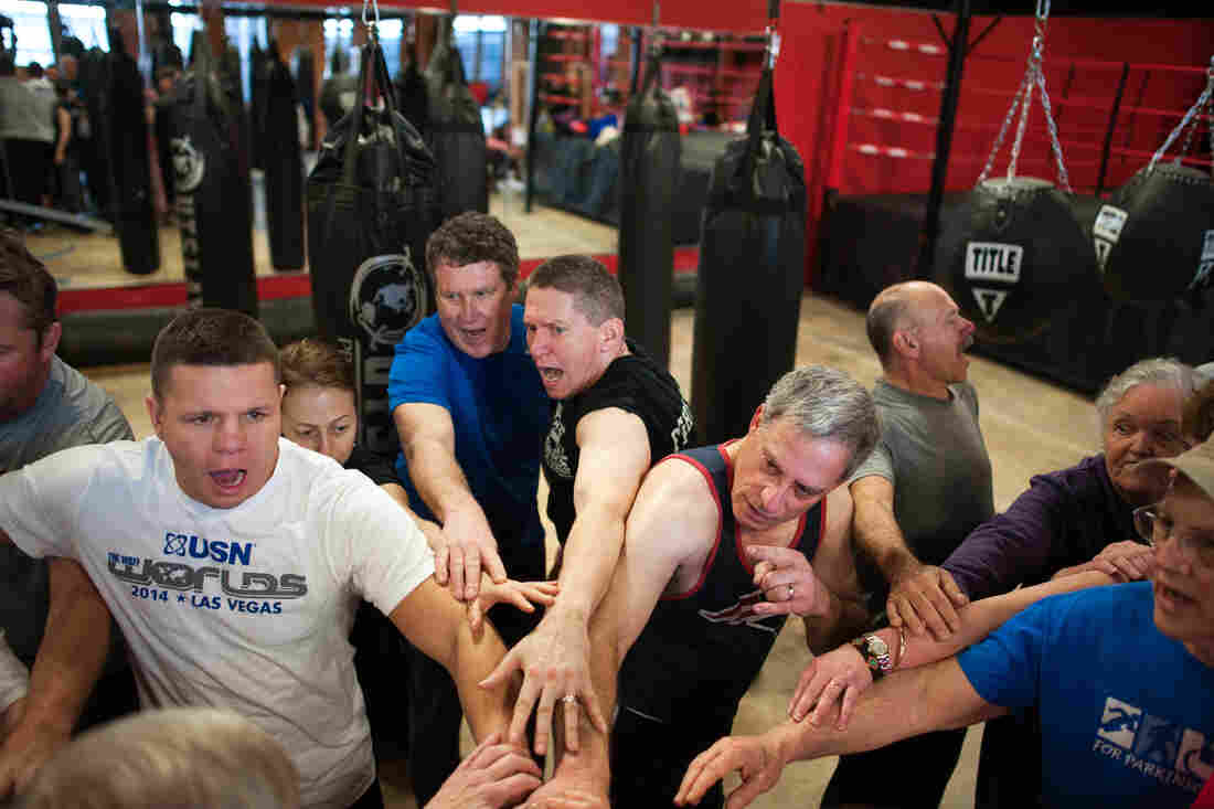"""Quaglia, center, joins a """"Rock Steady"""" cheer at the end of a boxing class."""