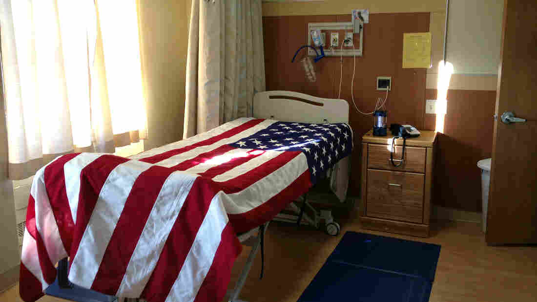 A hospital bed is draped with a flag after a veteran died in the hospice ward at St. Albans VA in Queens, N.Y.