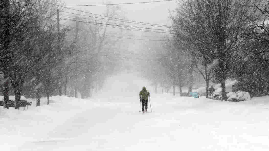 Francisco Fernandez de Alba skis along a recently plowed road during a snowstorm in Providence, R.I., Tuesday. Parts of the state were buried under nearly two feet of snow by early Tuesday afternoon, and more was on the way.