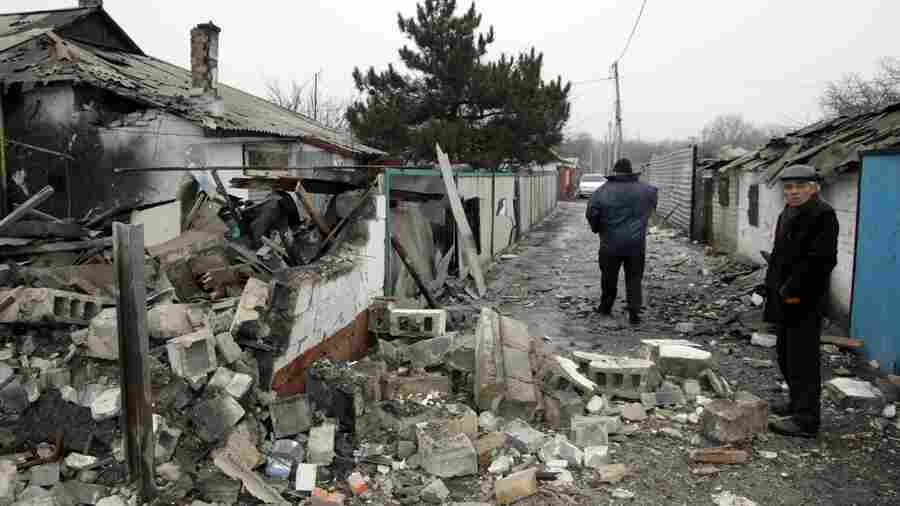 Residents assess the damage caused by shelling between the Ukrainian army and pro-Russian separatists on Wednesday in the eastern Ukrainian city of Donetsk.