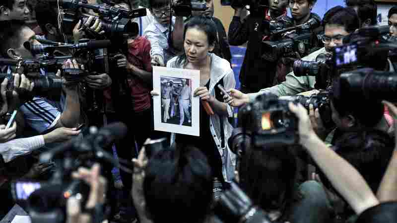 "A relative of a passenger of the missing Malaysia Airlines Flight 370 holds a picture of Malaysian Prime Minister Najib Razak with the writing ""Please bring back my husband."""