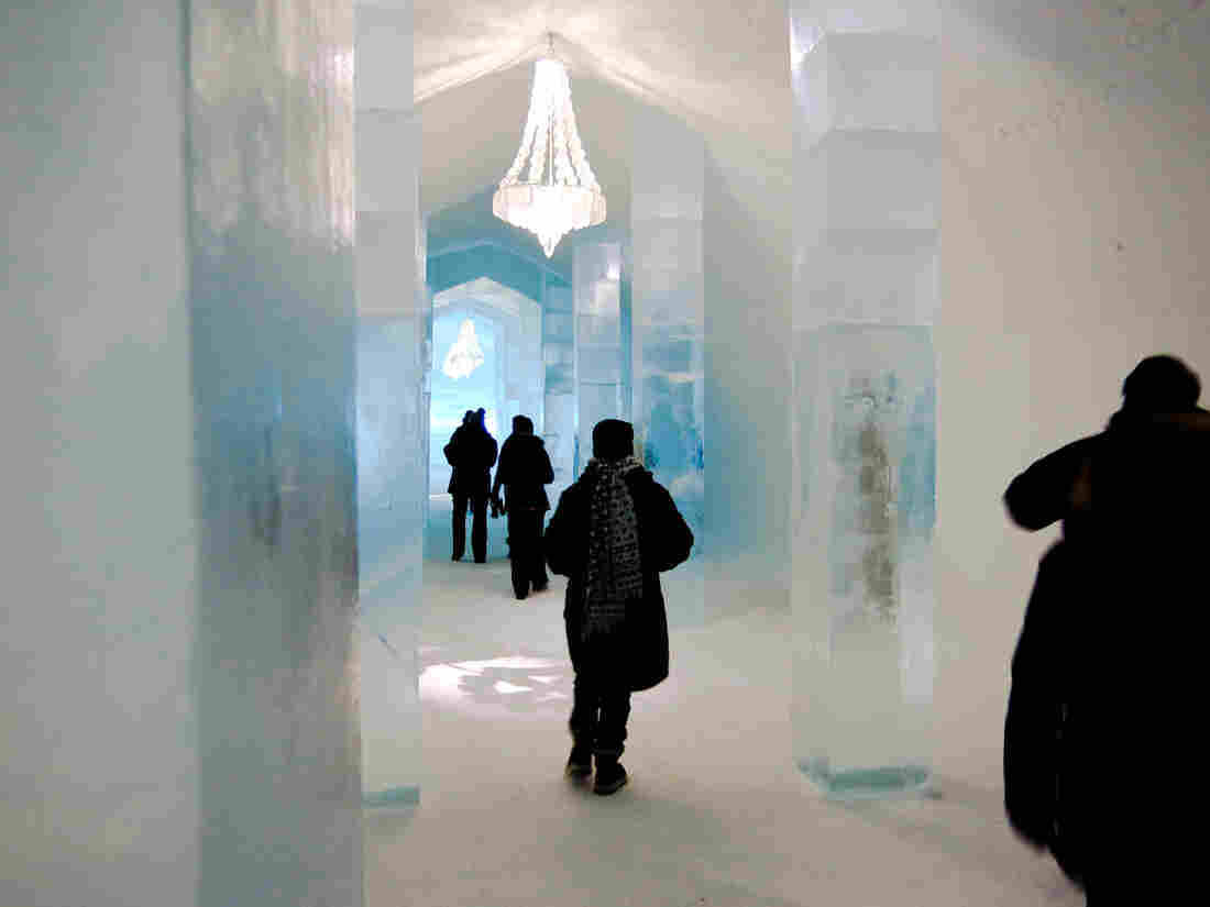 Visitors walk past icy decorations at Icehotel. Artists from around the world compete for the chance to design rooms in the Swedish landmark, and every year the hotel is rebuilt from scratch, with new sculptures.