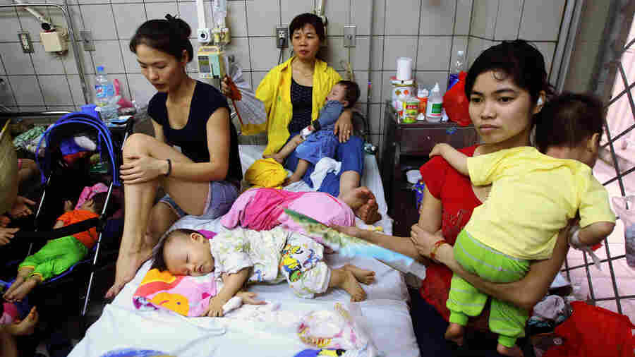 Measles brought these kids to a state-run hospital in Hanoi, where their family members offer comfort.