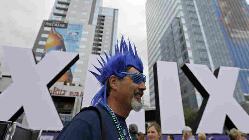 Steve Bronson, from Tempe, Ariz., walks past Roman numerals for the NFL Super Bowl XLIX, on Thursday.