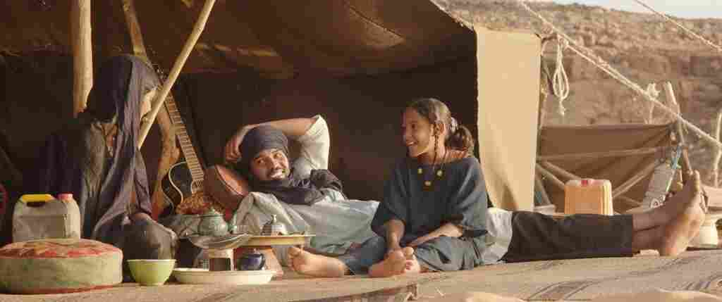In the film Timbuktu, Kidane (played by Ibrahim Ahmed, center) and his wife live in a tent on a dune outside the city with their daughter (played by Layla Walet Mohamed, right) and a boy orphaned by war, raising cows.