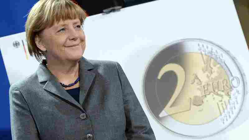 German Chancellor Angela Merkel stands in front of a poster showing a new Two-Euro commemorative coin at the Chancellery in Berlin, Germany, on Thursday.