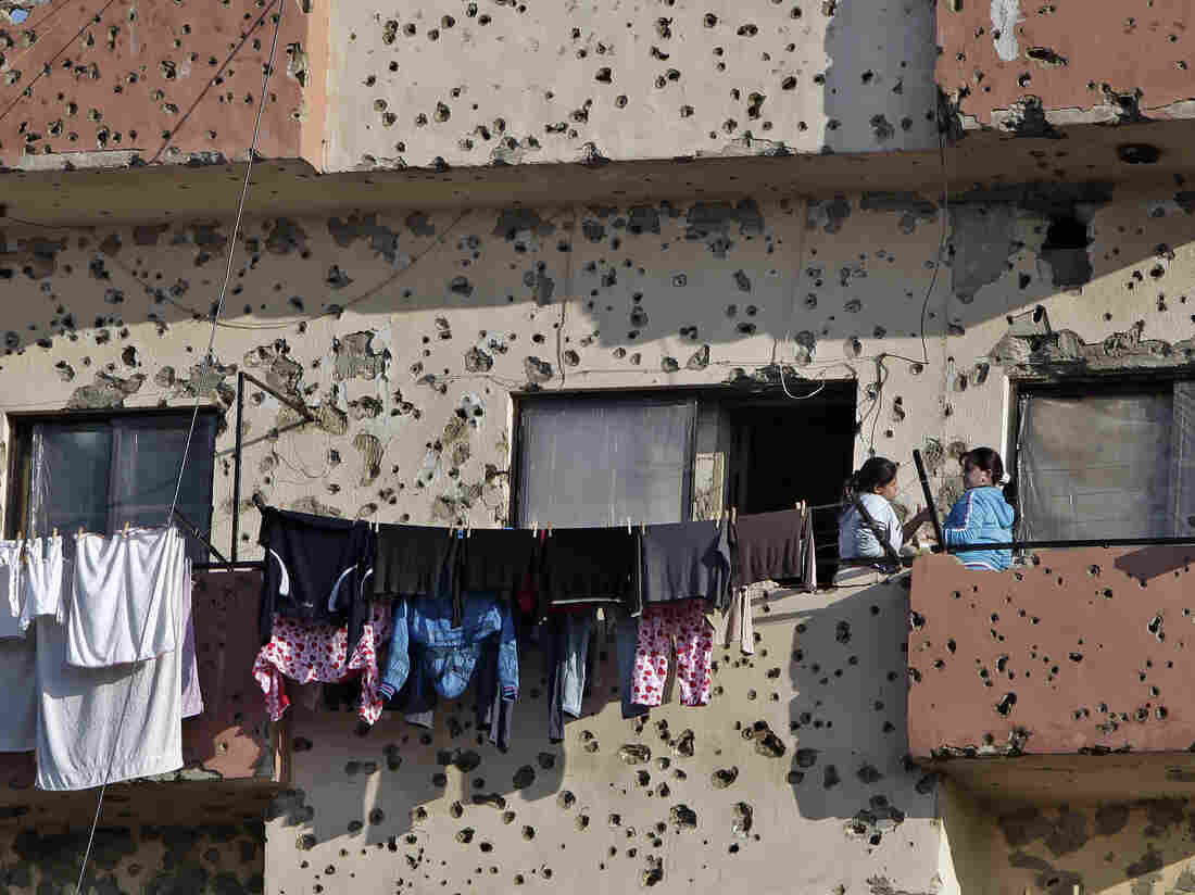 Bullet holes from recent clashes riddle an apartment building in Tripoli.