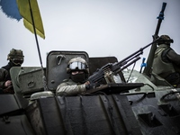 Ukrainian soldiers are seen in an armored vehicle topped with a Ukrainian flag near the city of Artemivsk, in the Donetsk region, on Sunday.