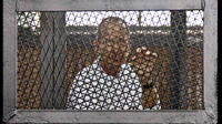 Al-Jazeera's Australian correspondent Peter Greste, seen here at a court room during trial in Cairo, Egypt, was released and deported Sunday.