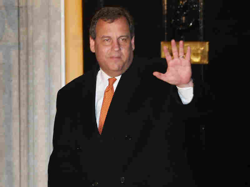 New Jersey Gov. Chris Christie waves to reporters as he leaves Downing Street in London on Monday.