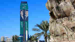 Advertising on a skyscraper in Manama, Bahrain, shows news anchors for the newly launched Al-Arab TV network. The pan-Arab channel began broadcasting Sunday but was suspended Monday after it aired an interview with a critic of Bahrain's monarchy.
