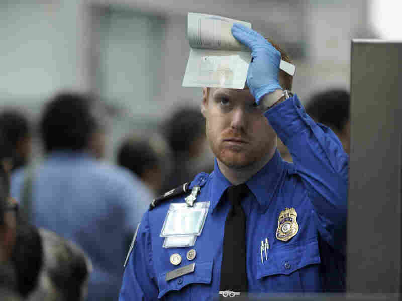 A security officer checks a passport at Chicago O'Hare International Airport.