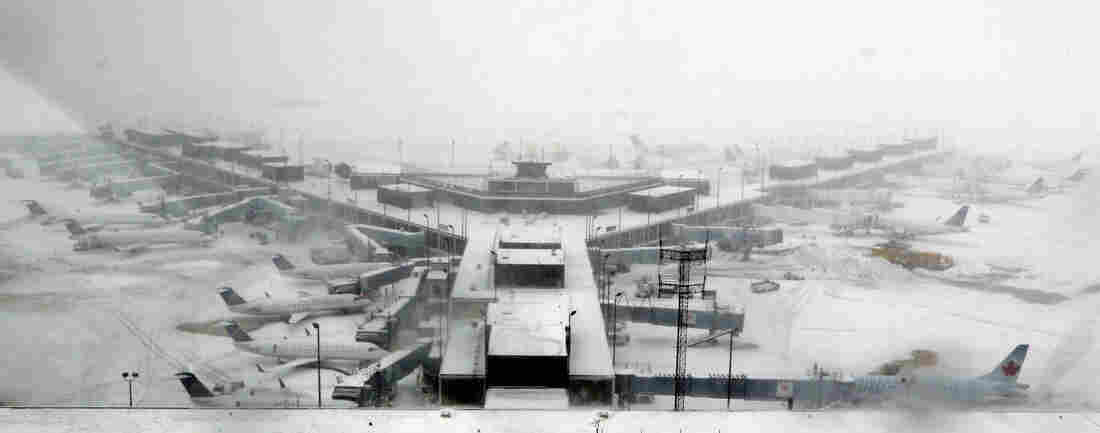 Airplanes stand in the snow at O'Hare International Airport on Sunday in Chicago. The city received 19 inches of snow from a storm that is now in the Northeast.