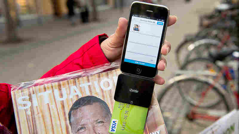 Nina Galata displays her smartphone equipped with a card reader to accept donations and payment for Situation Stockholm, a magazine sold by Stockholm's homeless.
