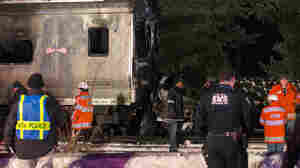 Emergency workers stand near a burned-out SUV that was struck Tuesday night by a Metropolitan Transportation Authority Metro-North Railroad commuter train near the town of Valhalla, N.Y.