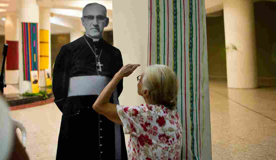 A Catholic faithful looks at a portrait of Monsignor Oscar Arnulfo Romero at his grave in the cathedral of San Salvador on March 24, 2014, during the commemoration of the 34th anniversary of his murder.